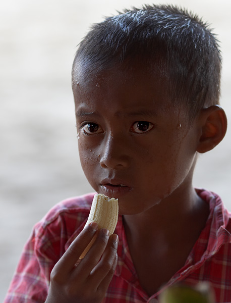 Enjoying a banana.  A young boy in Carita, Java.