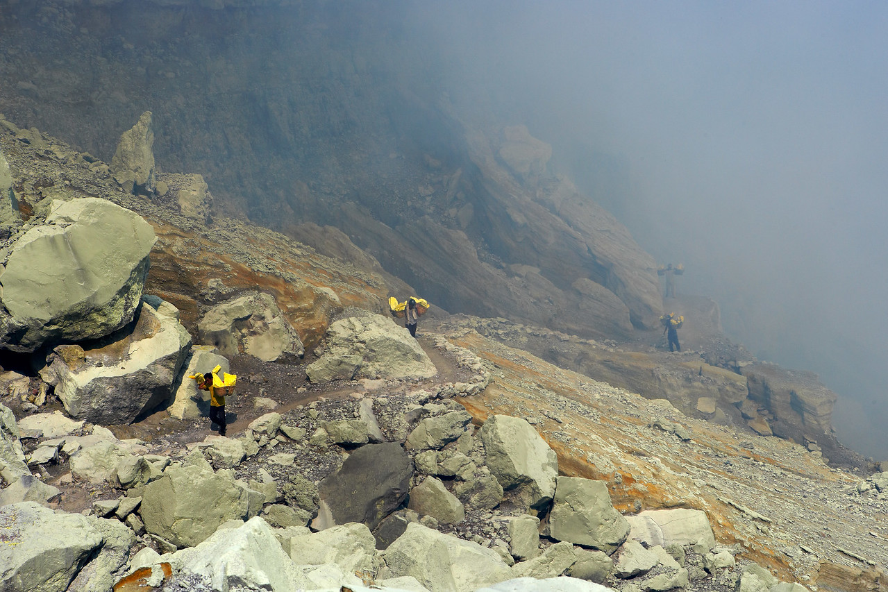 The ascent from the abyss.  Miners carry their loads up the trail that leads out of the Ijen crater.  It takes about 4 hours to carry one load out of the crater.  The fog contains a high concentration of sulphur dioxide which doesn't make breathing any easier.